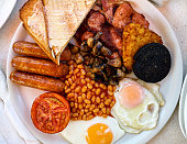 Traditional full english breakfast. Fried eggs, baked beans, bacon, sausages and toasts