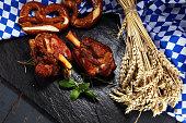Traditional German cuisine, Schweinshaxe roasted ham hock. pretzels Bavarian specialties. Oktoberfest background with pork  knuckle