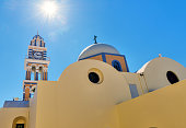 View of traditional Greek architecture: domes and bell towers, in the island of Santorini, with sunny sky.
