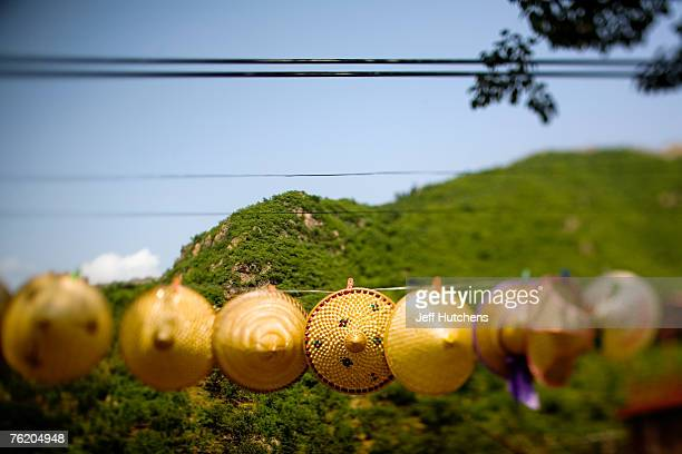 Traditional hats hang for sale under power lines near a decrepit section of the Great Wall on June 30 2006 outside of Beijing China China continues...