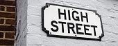 A simple British High Street sign on a painted brick wall.