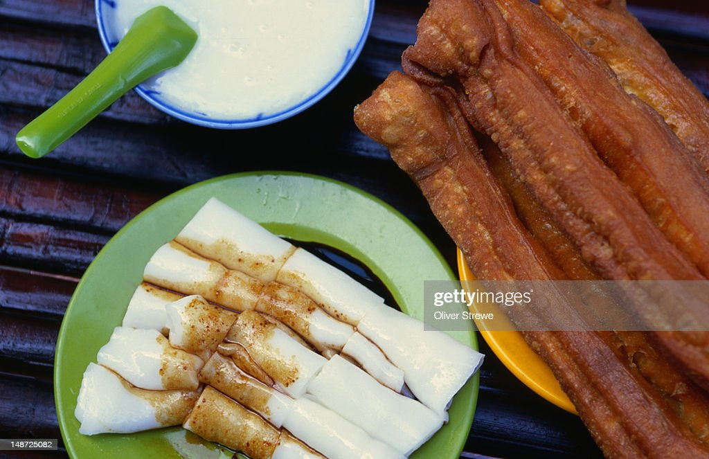 Traditional Hong Kong breakfast of congee and chinese donuts with rice rolls and soy sauce, congee rice soups are eaten from Japan to Persia as breakfasts, snacks and with other dishes : Stock Photo