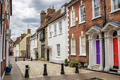 Traditional houses on a cobbled street in Poole, England, on a cloudy day