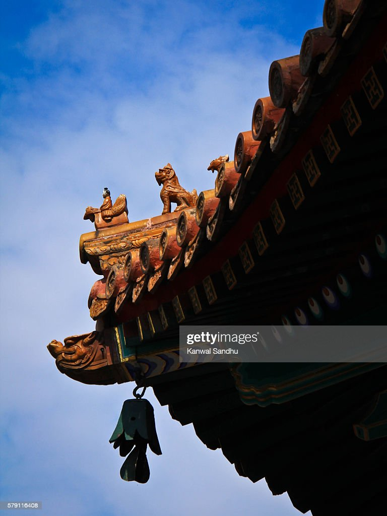 Traditional Imperidal curved chinese yellow roof tile design representing a deity riding a mythical bird