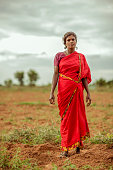 Traditional Indian mid age women in red saree standing on farm land, India.