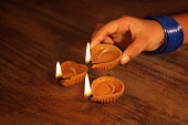Traditional Indian oil lamps burning on a wooden background. Concept for Diwali festival of India.