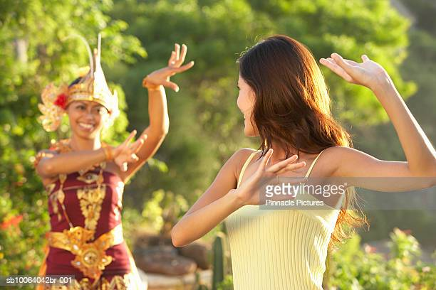Traditional Indonesian dancer teaching tourist to dance