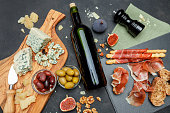 Traditional italian food - prosciutto, cheese, wine, olives and bread on concrete background