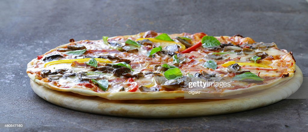 traditional Italian pizza with mushrooms, peppers and pancetta : Stock Photo