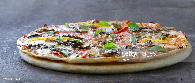 pizza italiana tradicional con champiñones, pimientos y panceta : Foto de stock