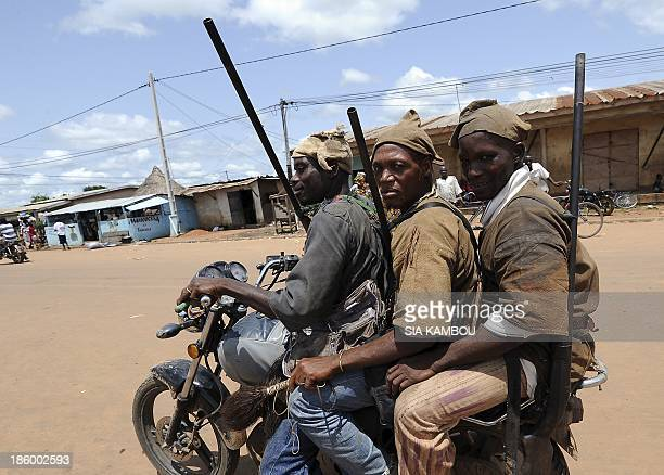 Traditional Ivorian Dozo hunters members of the Binkadi association that gathers all Dozos in the region ride a motorbike as they arrive on September...