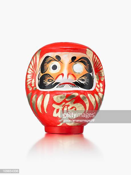 A Traditional Japanese Daruma Doll on a White Background