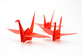 Traditional Japanese origami crane made of red paper over white background
