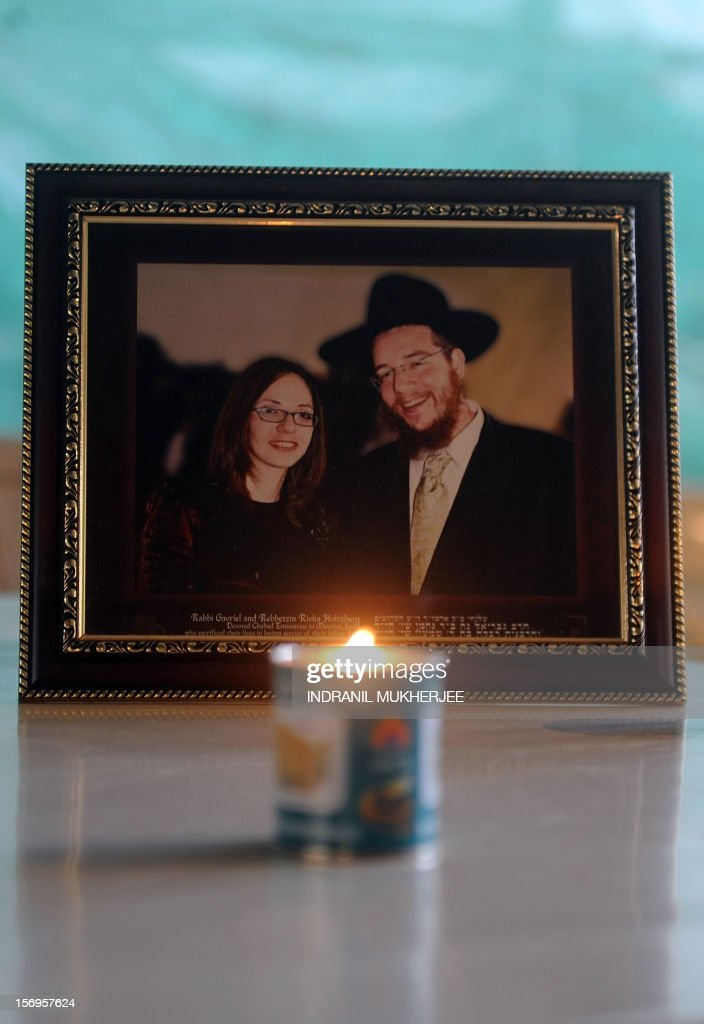 A traditional Jewish memorial candle is seen placed in front of a photograph of slain Rabbi Gavriel Holtzberg and his wife Rivkah, at the Chabad (Nariman) house in Mumbai on November 26, 2012. The Holtzbergs were killed in the attacks on Mumbai while the couple's son Moshe was rescued by their nanny. A total of 166 people were killed and more than 300 others were injured when 10 heavily-armed Islamist militants stormed the city on November 26, 2008, attacking a number of sites, including the city's main railway station, two luxury hotels, a popular tourist restaurant and a Jewish centre.