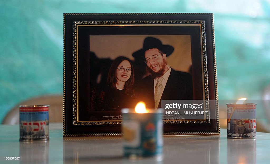 Traditional Jewish memorial candles are seen placed in front of a photograph of slain Rabbi Gavriel Holtzberg and his wife Rivkah, at the Chabad (Nariman) house in Mumbai on November 26, 2012. The Holtzbergs were killed in the attacks on Mumbai while the couple's son Moshe was rescued by their nanny. A total of 166 people were killed and more than 300 others were injured when 10 heavily-armed Islamist militants stormed the city on November 26, 2008, attacking a number of sites, including the city's main railway station, two luxury hotels, a popular tourist restaurant and a Jewish centre.