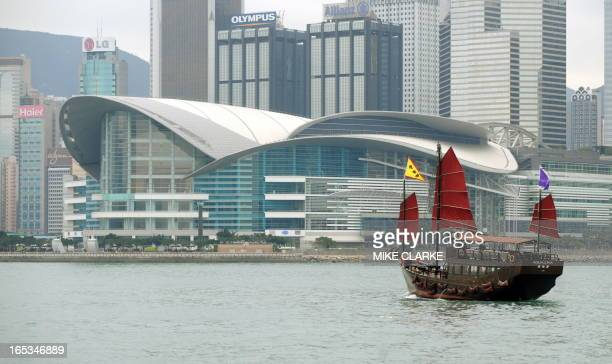 A traditional junk nowadays mostly used for private functions and advertising sails on Victoria Harbour against a backdrop of the Hong Kong...