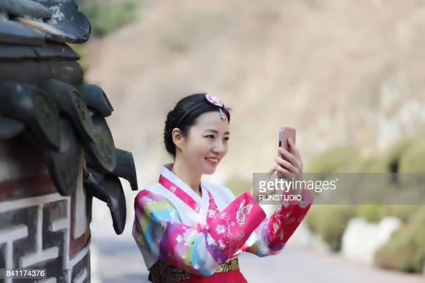 traditional Korean woman using smartphone