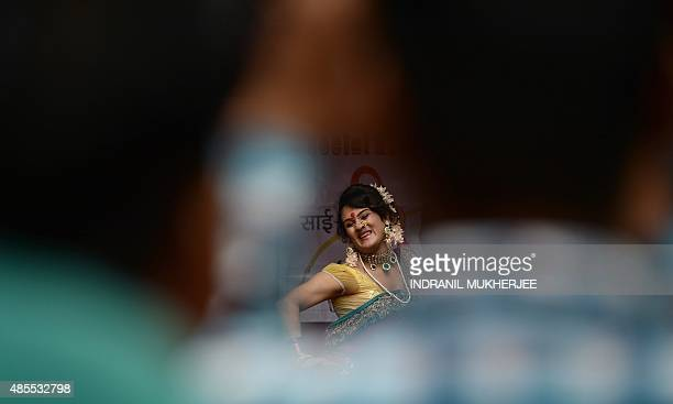 A traditional Lavani folk dancer is seen through a gap among the audience during a performance for sex workers in the red light district of...