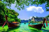 Two longtail boats in the shade at Railay beach, Ao Nang, Thailand