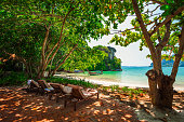 View of beach chairs and traditional longtail boat at Railay beach, Ao Nang, Thailand