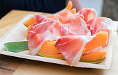Cured meats of prosciutto and slices of cantelope melon on a white platter, a traditional lunch or appetizer served in  Cinque Terre; Italy; Europe;