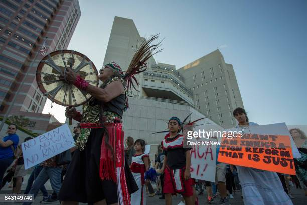 Traditional Mayan dancers march past the Metropolitan Detention Center as undocumented people jailed inside tap on the windows in opposition to the...