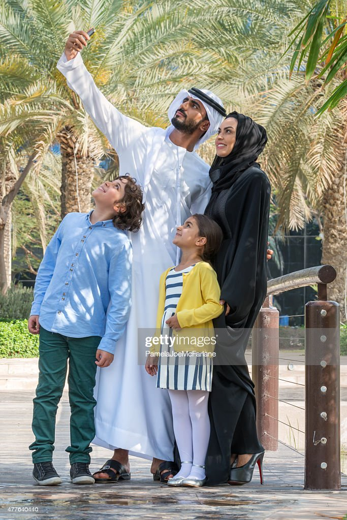 Traditional Middle Eastern Family of Four Taking Selfie in Park