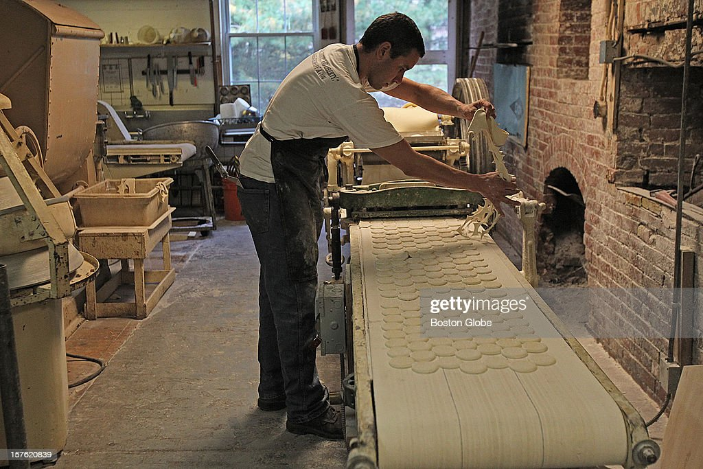 Traditional New England common cracker which is made on old equipment at the G.H. Bent Co. The making of the G. H. Bent Common Cracker, by owner Jim Davis and his assistant Ian Hildred, Owner, Davis, pulls the excess dough after the crackers have been cut.