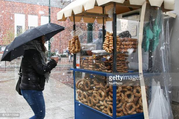 Traditional obwarzanek sold from a stall during heavy snow in spring time in Krakow Poland on 19 April 2017