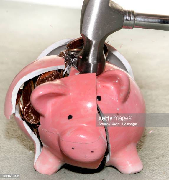 A traditional piggy bank is smashed open with a hammer