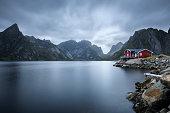 Traditional red rorbu cottage under the  mount Olstind in Hamnoy village, Lofoten islands, Norway. Long exposure.