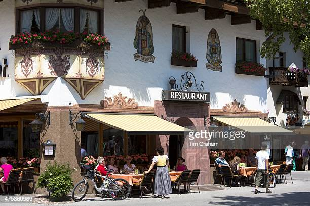 Traditional restaurant and waitress in dirndl dress in main plaza of the town of Seefeld in the Tyrol Austria