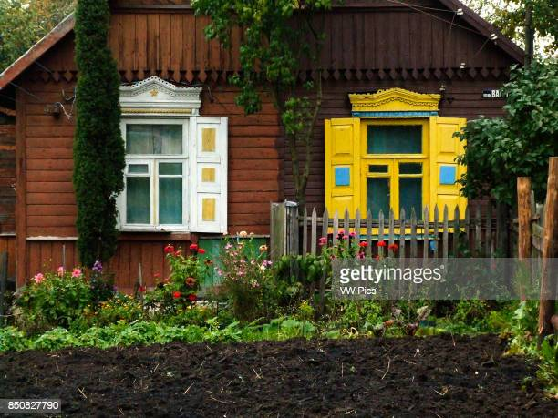 A traditional Russian house made of wood or timbers and with nalichniki fancy decorative wood trim around the windows This style of house is...