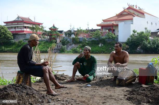 Traditional sand miners preparing to dive in the Brantas River with the Tjoe Hwie Kiong temple in the background The miners dive into the river to...