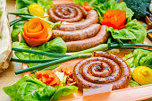 Decorated sausages with fresh vegetables are exposed on traditional sausage tournament.