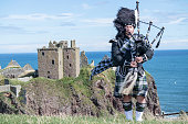 Traditional scottish bagpiper in full dress code at Dunnottar Castle