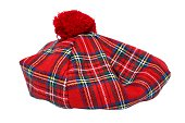 Traditional Scottish Red Tartan Bonnet, also named Tam o' Shanter. Men headgear Isolated on white Background.