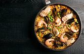 Traditional seafood paella in the pan on a wooden table