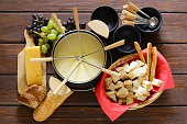 Traditional set of utensils for fondue, with bread, cheese, grapes