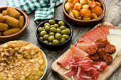 Traditional spanish tapas. Croquettes, olives,  ham and patatas bravas on wooden background