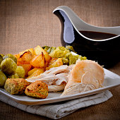 Chicken Sunday lunch with gravy boat potatoes vegetables stuffing and sprouts