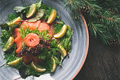 A traditional Swedish Christmas dinner with gravlax on a wooden table. Decorated with pine needles and candles.