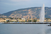 Traditional Swiss residential apartment blocks sit on the bank overlooking Lake Geneva as the Jet d'Eau water fountain rises in Geneva Switzerland on...