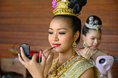 Traditional Thai ladies with her friend making up for the show and photographers who come to shoot them, beautiful girls sitting in a wood house putting lipstick on with beautiful dresses and jewelry