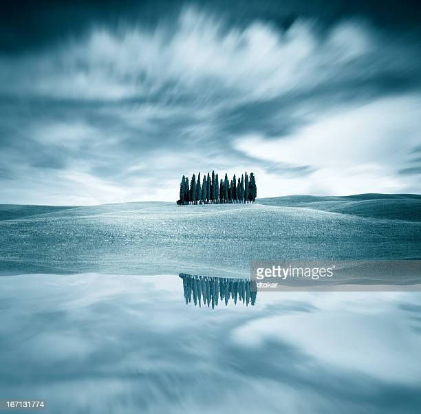 Traditional Tuscany landscape with trees and reflection in water