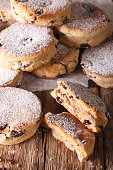 Traditional Welsh cakes with raisins and powdered sugar macro on the table. vertical