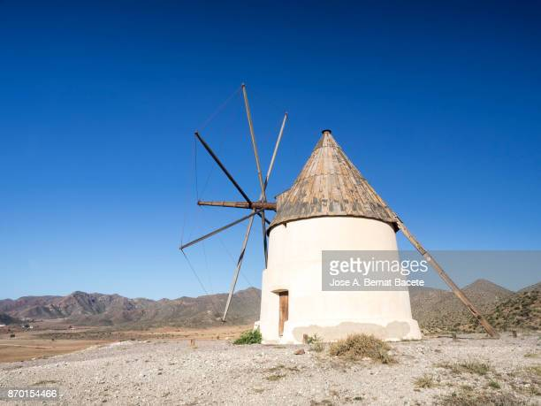 Traditional windmill among mountains in a sunny arid area with a blue sky. Natural Park of Cabo de Gata - Nijar, in Almeria,  Andalucia, Spain.