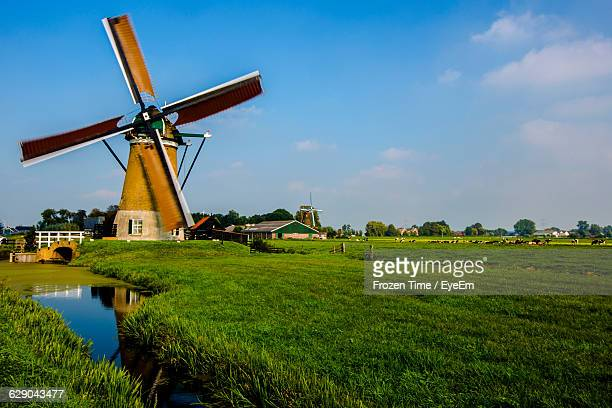 Traditional Windmill On Grassy Field Against Sky