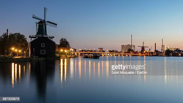 Traditional Windmills By River Against Sunset Sky