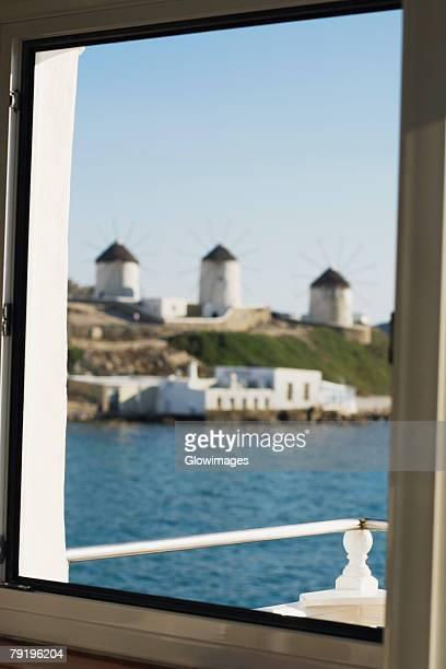 Traditional windmills viewed through a window, Mykonos, Cyclades Islands, Greece